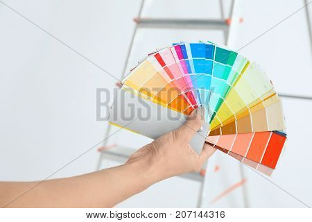 Young female decorator with color palette samples near ladder on white background