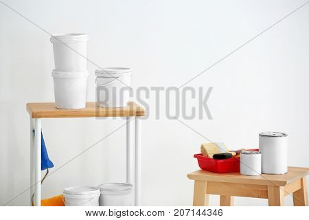 Many paint buckets and decorator's tools indoors