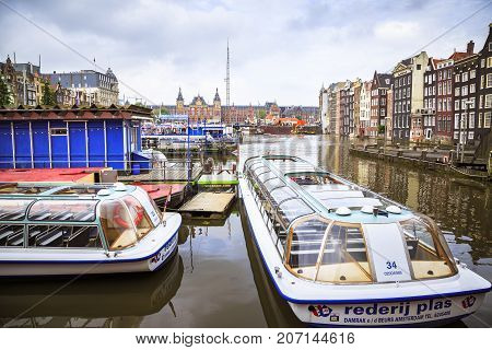 AMSTERDAM NETHERLANDS - JUNE 21 2016: One of Amsterdam's canal with tourism boats and the Amsterdam Centraal in the background a cloudy day. Amsterdam Netherlands.