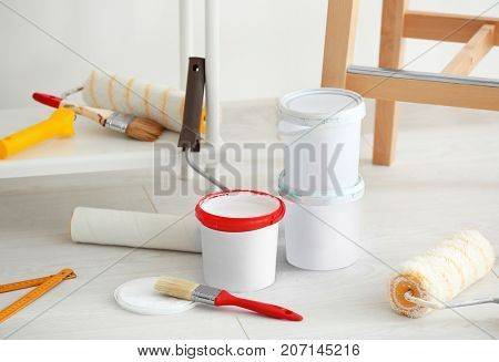 Decorator's tools and paint on floor indoors