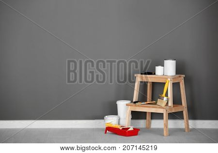 Composition with paint and decorator's tools near wall