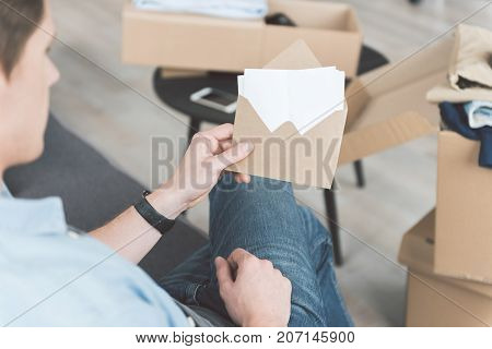 Close up man hand keeping envelope. He looking through it. Post concept. Top view