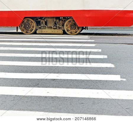 Fragment of the tram moving the crosswalk. Two wheels and a magnetorail brake between them. Background.
