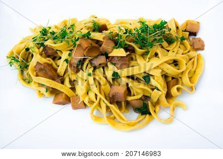 Italian dish: Fresh handmade tagliatelle pasta with porcini mushrooms isolated on white