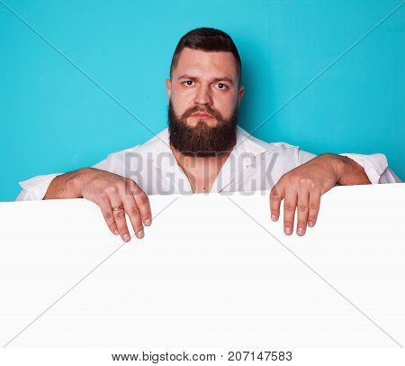 handsome young man with long beard and moustache on face with pointing finger on blue background in studio