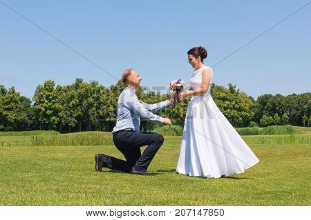 Man makes a proposal to his girlfriend to get married. Marriage proposal. Love and marriage concept. Young attractive cheerful couple in the park
