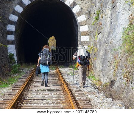 Family tourists with backpacks on railroad track
