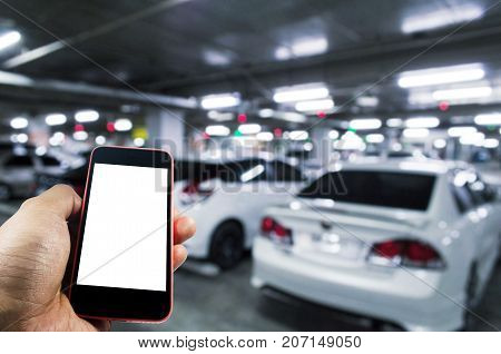 hand using mobile smart phone with blurred image of indoor car parking garage area RFID solution management system internet social media and car parking sensor technology concept