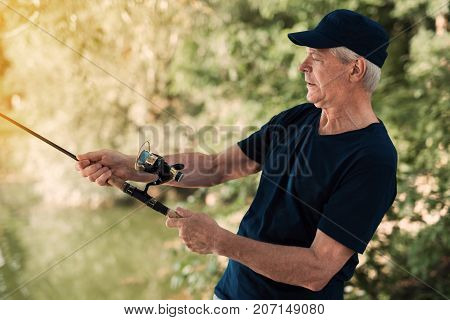 The Old Man In A Black T-shirt Is Standing On The River Bank And Holding A Spinning. He Seems To Hav