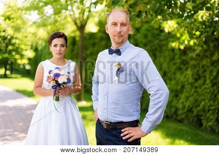 Happy just married young wedding couple having fun in the park. Bride and groom together, love and marriage theme