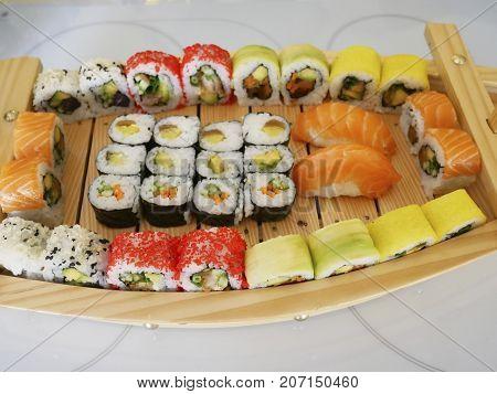 several kinds of sushi on a wooden platter