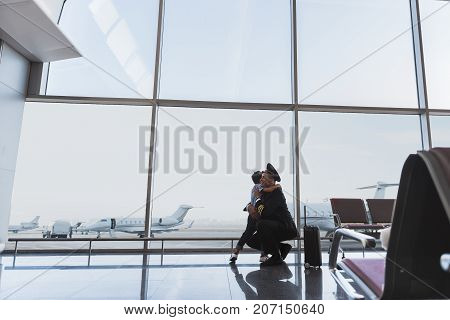 Aviator is squatting and embracing little child. They locating near glass wall at terminal. Copy space on left side