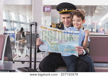 Cheerful aviator is holding unfolded map and reading it with joyous son sitting on laps of father. They locating in airport. Copy space on right side. Portrait
