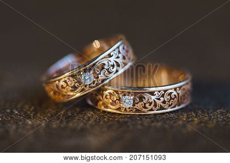 Carved wedding rings lie on a brown velvet background