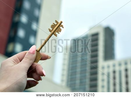 a female hand holds the keys against the background of new buildings