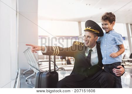 Look there is my plane. Happy pilot is squatting near son and pointing aside. They looking at window with bright smile. Copy space on left side