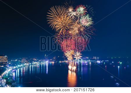 Fireworks over the sea beach with blue twilight sky background and city view
