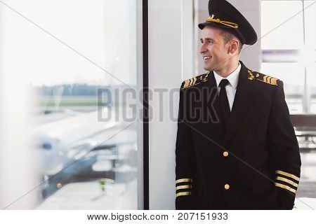 Joyous aviator is leaning against glass wall and looking at planes with wide smile. Waist-up portrait. Copy space on left side