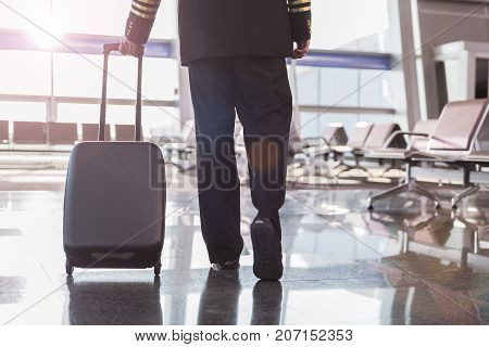 Aviator is carrying suitcase and ready for doing his work. Close up of suitcase. Copy space on right side
