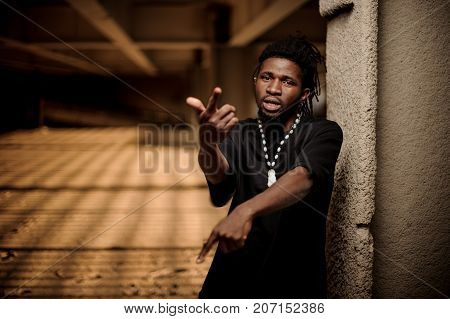Portrait of the gesticulating afro american man with dreadlocks and dressed in the black t-shirt