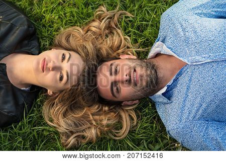 Top view of two friends smiling while looking towards the sky as they laying at the grass