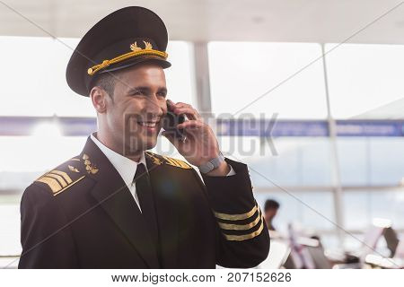 Cheerful pilot wearing uniform is speaking on smartphone and looking ahead with bright smile. Waist up portrait. Copy space on right side