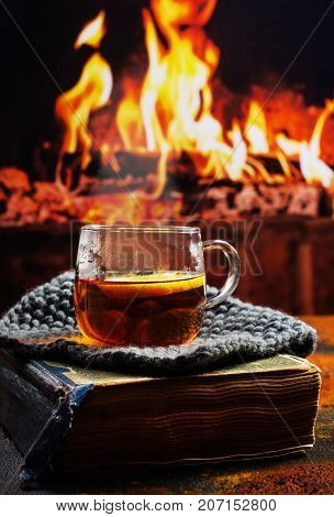 Hot tea with lemon, old vintage book near fireplace. Cozy winter evening near fireplace. Copy space