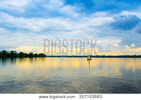 Hamburg Germany - 18 September 2017: Sailboat s on the water of Lake Alster with cloudy autumnal landscape on background