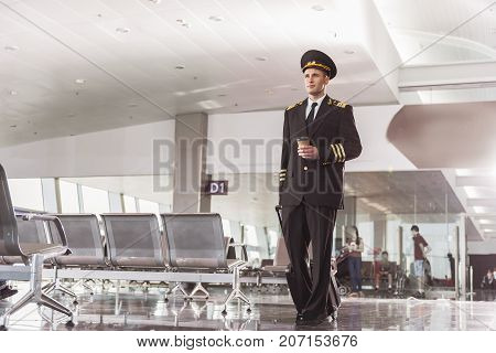 Confident pilot is walking through waiting hall of airport and carrying suitcase. Full length portrait. Low angle. Copy space on left side