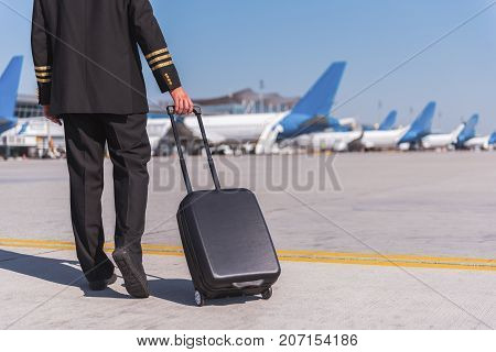Pilot wearing uniform is looking ahead with confident smile. He standing afore aircrafts. Full length portrait. Copy space on right side