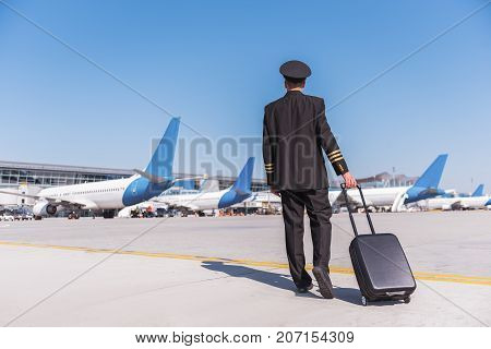 Aviator wearing uniform is going to planes through runway. Copy space on left side