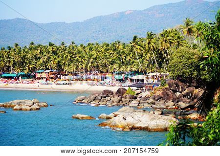 Palolem beach, South Goa, India. One of the best beaches in Goa. Colorful beach huts and palm trees on the coast. Luxury leisure.