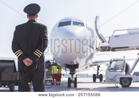 Pilot wearing uniform is standing outside and looking at plane. He turning back to camera. Copy space on right side