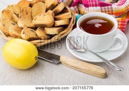 Rusks With Raisin In Wicker Basket, Tea, Lemon, Knife