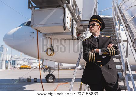 Proud pilot standing on gangway and looking aside. Portrait. Copy space on left side. Low angle