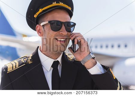 Glad aviator wearing uniform is using smartphone for conversation. He looking ahead with smile. Portrait