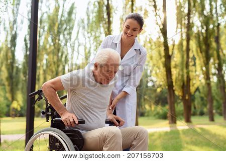 Care Helps Cure All Ailments. The Doctor Helps The Patient To Get Up From The Wheelchair