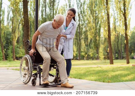 The Doctor Helps The Patient To Get Up From The Wheelchair And Walk