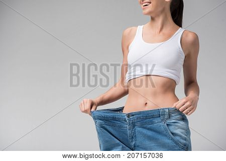 I lost my weight. Close up of fit body of happy young woman wearing oversized jeans and smiling. Isolated and copy space