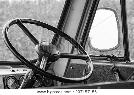 The steering wheel in the cockpit of an old car. Retro style. Black and white photo