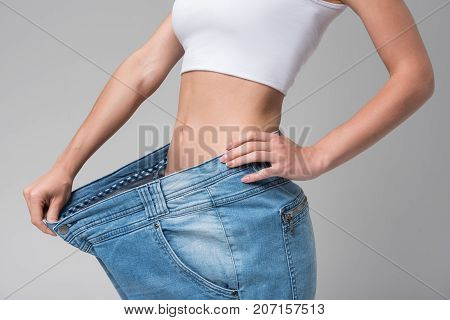 Close up of slim waist of young woman wearing oversized jeans. She is pulling off the texture in the way to show the great result of her dieting