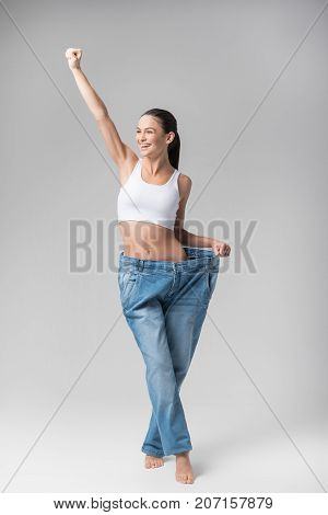 Finally I am slim. Full length portrait of happy girl raising hand up with excitement and laughing. She is wearing oversized jeans to show result of diet. Isolated