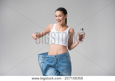 Keep on the diet and be like me. Portrait of excited girl is pointing at her slim waist and oversized pants. She is holding bottle of water and smiling. Isolated