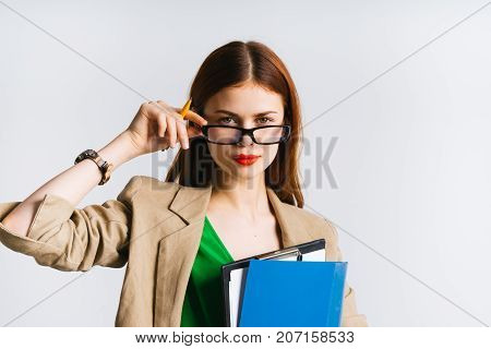 girl secretary with files in her hand adjusts her glasses