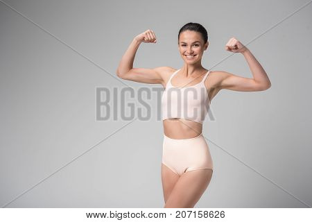 I am fit and strong. Portrait of happy slim girl in tight high waist underwear and showing her muscles on arms. She is standing and smiling. Isolated and copy space