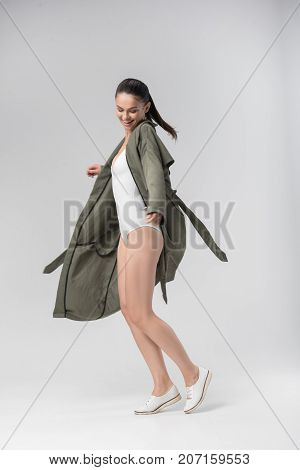Cheerful young fit woman is dancing and smiling. She is wearing coat with underwear and looking at her figure with satisfaction. Isolated
