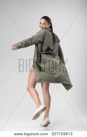 Full length of fit excited girl posing in coat. She is looking back at camera and laughing. Isolated