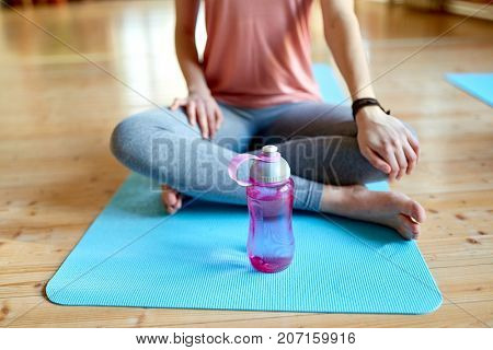 fitness, sports accessories and healthy lifestyle concept - woman with water bottle resting on yoga mat in gym or studio