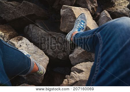 the legs of a young tourist in front of a lake in the holidays on a shore
