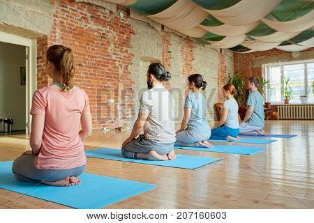 fitness, sport and healthy lifestyle concept - group of people doing yoga seated kneeling pose on mats at studio
